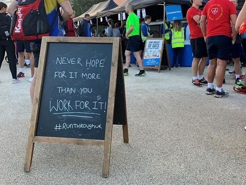 Blackboard sign at event: Never hope for it more than you work for it! #RunThroughUK