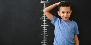 Young boy measures his height against blackboard